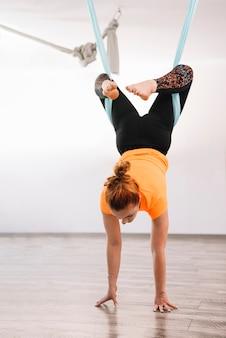 Jonge gezonde vrouw die antigravity yoga doet die blauwe hangmat gebruikt