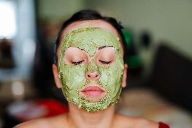 Jonge gezonde vrouw die behandelingen en het masker van de gezichtsklei maakt.