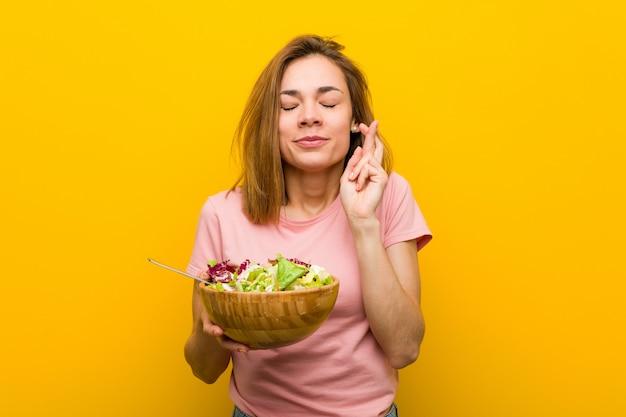 Jonge gezonde vrouw die een salade houdt die vingers kruist voor het hebben van geluk