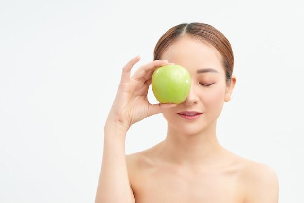Jonge gezonde vrouw die groene appel over haar ogen op witte muur houdt