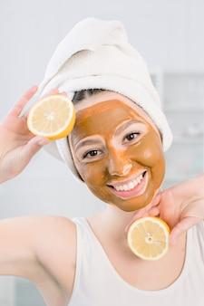Jonge gezonde vrouw die in kuuroord behandelingen en het masker van de gezichtsmodder maken.
