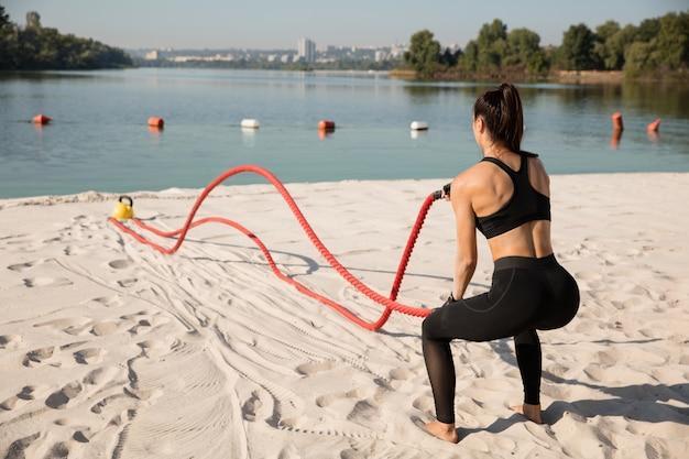 Jonge gezonde vrouw die oefening met de touwen doet op het strand.