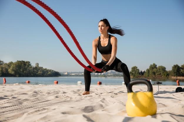 Jonge gezonde vrouw die oefening met de touwen doet op het strand