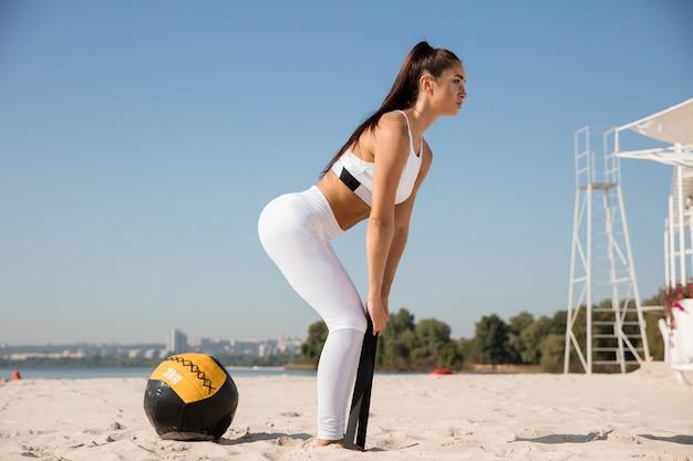 Jonge gezonde vrouw die zich uitstrekt met de bal op het strand.