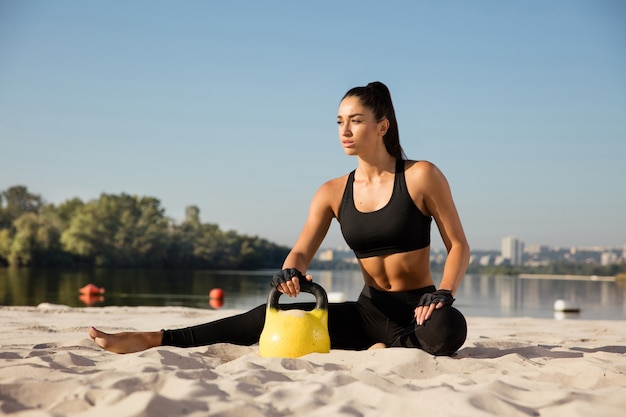 Jonge gezonde vrouw die zich uitstrekt met gewichten op het strand.