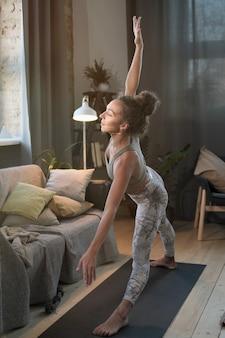 Jonge gezonde vrouw die zich uitstrekt tijdens sporttraining in de kamer