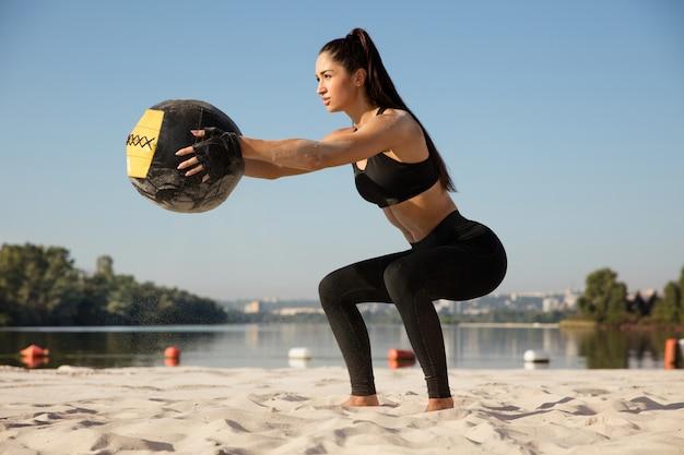 Jonge gezonde vrouw doet kraakpanden met bal op het strand