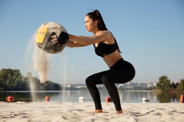 Jonge gezonde vrouw doet kraakpanden met de bal op het strand.