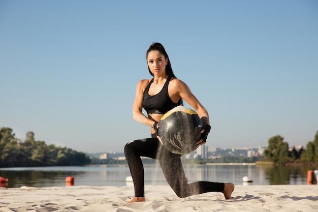 Jonge gezonde vrouw doet lunges met bal op het strand