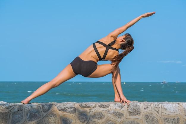 Jonge gezonde vrouw het praktizeren yoga op het strand op blauwe hemelachtergrond.