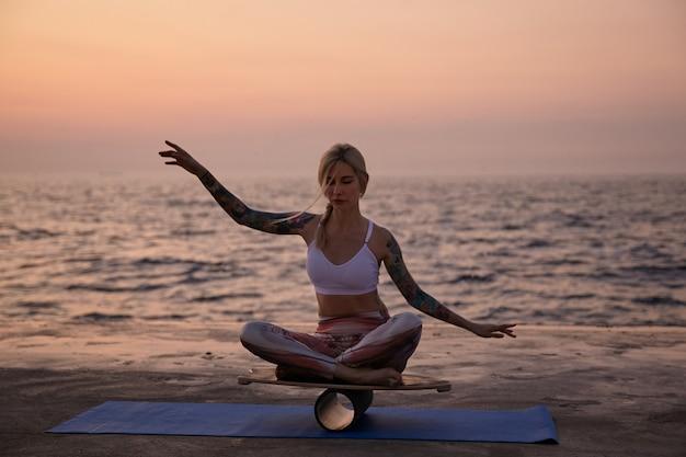 Jonge gezonde vrouw met casual kapsel zittend op een houten bureau en balanceren met handen, op zoek geconcentreerd en kalm, poseren over zee uitzicht op de vroege ochtend