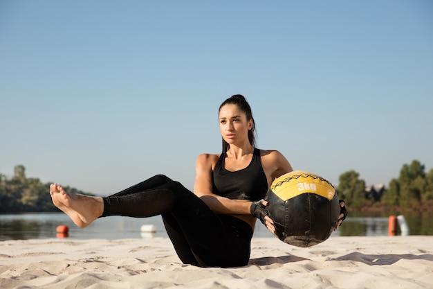 Jonge gezonde vrouw opleiding bovenlichaam met bal op het strand.