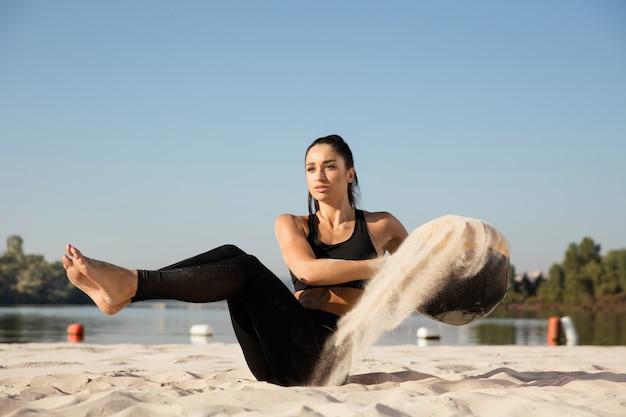 Jonge gezonde vrouw opleiding bovenlichaam met bal op het strand