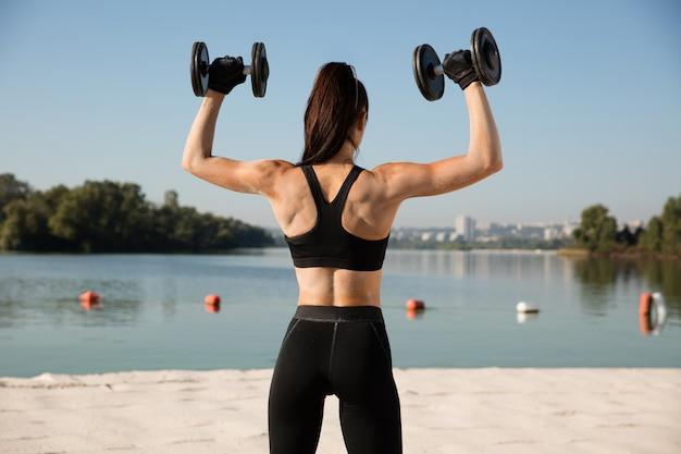 Jonge gezonde vrouw opleiding bovenlichaam met gewichten op het strand.