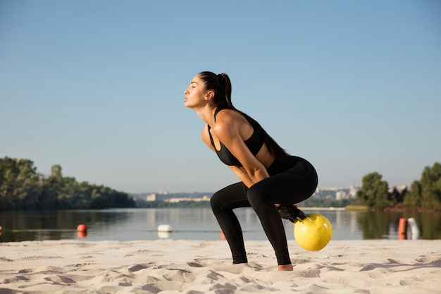 Jonge gezonde vrouwelijke atleet training op het strand