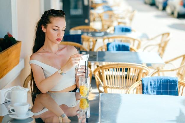 Jonge glamour sexy vrouw die mobiele telefoon bekijkt