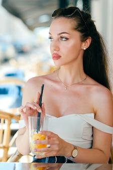 Jonge glamour sexy vrouw poseren met sap