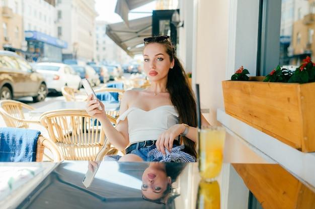 Jonge glamour sexy vrouw zittend in het café van de straat