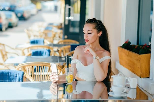 Jonge glamourvrouw die mobiele telefoon bekijkt