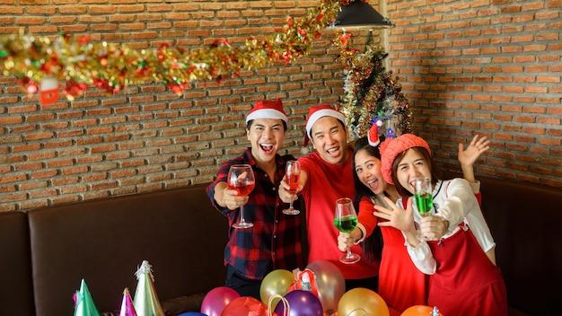 Jonge glimlach aziatische mannen en vrouwen met santa hoeden gerinkelglazen rode wijn