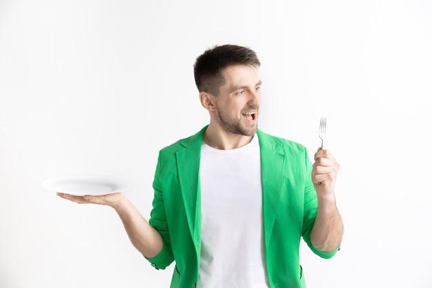 Jonge glimlachende aantrekkelijke kaukasische kerel die lege die schotel en vork houdt die op grijs wordt geïsoleerd