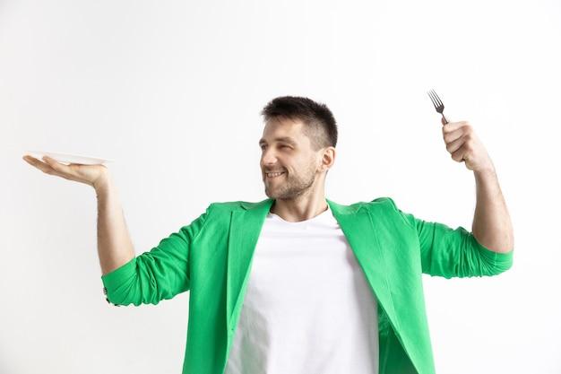 Jonge glimlachende aantrekkelijke kaukasische kerel die lege die schotel en vork houdt die op grijze ruimte wordt geïsoleerd. kopieer de ruimte en maak een mock-up
