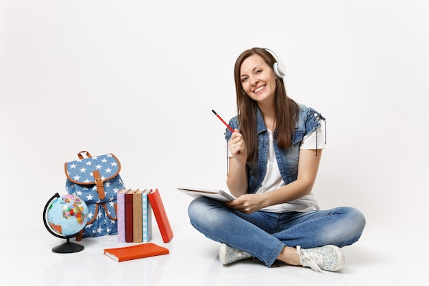 Jonge glimlachende aantrekkelijke vrouw student in koptelefoon luisteren muziek met notitieboekje, potlood in de buurt van globe, rugzak, schoolboeken geïsoleerd