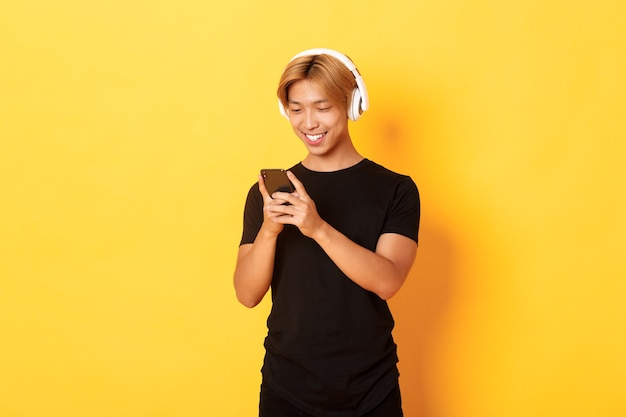 Jonge glimlachende aziatische kerel die smartphone gebruikt en muziek of podcast in draadloze hoofdtelefoons luistert