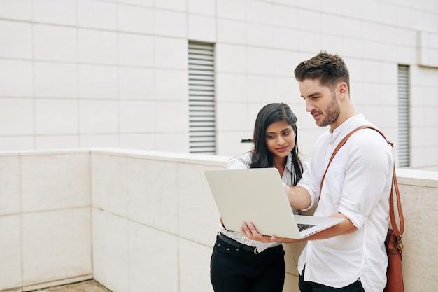 Jonge glimlachende bedrijfsmensen die e-mail lezen of op laptop het scherm rapporteren