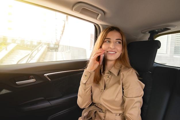 Jonge glimlachende bedrijfsvrouw die op de achterpassagiersstoel van haar auto zit en aan de telefoon onderhandelt. bedrijfsconcept