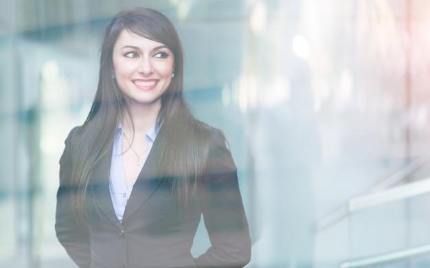 Jonge glimlachende bedrijfsvrouw, dubbel blootstellingseffect