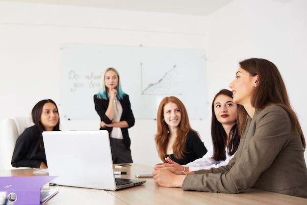 Jonge glimlachende bedrijfsvrouwen die nieuw project werken op kantoor.