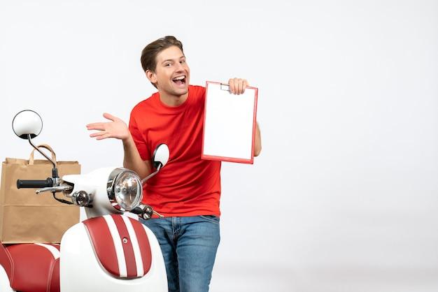 Jonge glimlachende bezorger in rode uniform staande in de buurt van het document van de scooterholding op witte muur
