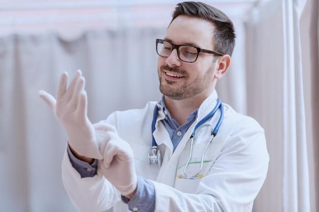 Jonge glimlachende blanke mannelijke arts in wit uniform, met bril en een stethoscoop om de nek, rubberen handschoenen zetten voor geduldig onderzoek.