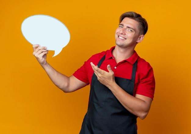 Jonge glimlachende blonde mannelijke kapper in uniform houdt en wijst op praatjebel geïsoleerd op oranje ruimte met kopie ruimte
