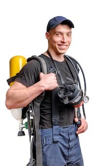 Jonge glimlachende brandweerman met een masker en een luchtpak op zijn rug in zwart t-shirt