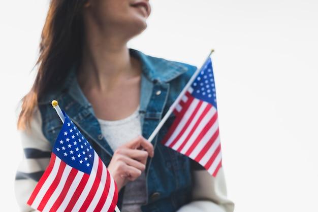 Jonge glimlachende dame die amerikaanse vlaggen houdt
