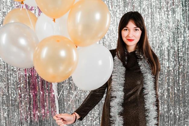 Jonge glimlachende dame die vele ballons dichtbij klatergoud houdt