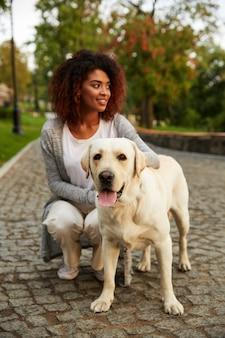 Jonge glimlachende dame in vrijetijdskleding die en hond in park zitten koesteren
