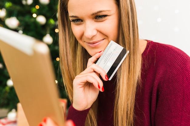 Jonge glimlachende dame met tablet en plastic kaart dichtbij kerstboom