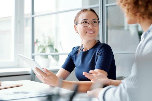 Jonge glimlachende elegante analist met touchpad die collega bekijkt terwijl hij naar haar mening over het onderwerp luistert