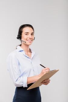 Jonge glimlachende elegante onderneemster in hoofdtelefoon die notities maakt tijdens het raadplegen van cliënten voor camera