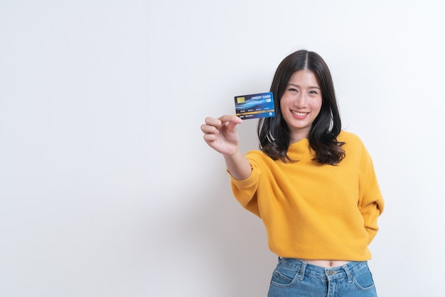 Jonge glimlachende en mooie aziatische vrouw die in hand creditcard voorstellen die vertrouwen en vertrouwen voor het doen van betaling tonen