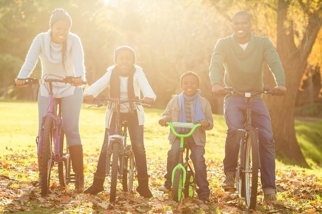 Jonge glimlachende familie die een fietsrit doet