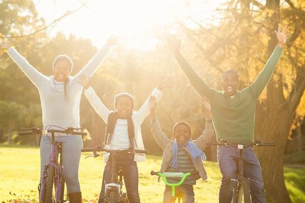 Jonge glimlachende familie die een fietsrit met opgeheven wapens doet