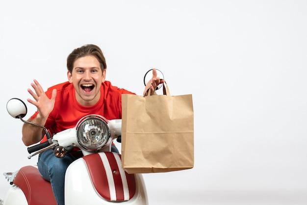 Jonge glimlachende gelukkige koerierskerel in rood uniform zittend op de papieren zak van de autopedholding op witte muur