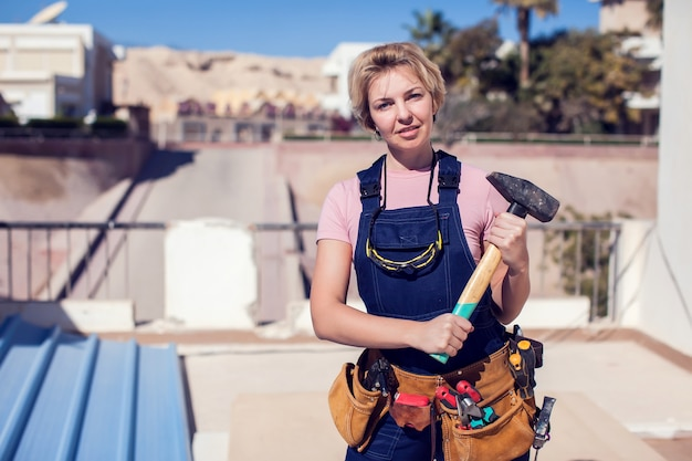 Jonge glimlachende handige vrouw met kort blond haar die met hamer werkt.