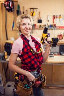 Jonge glimlachende handige vrouw met kort blond haar die met schroevedraaier werkt.