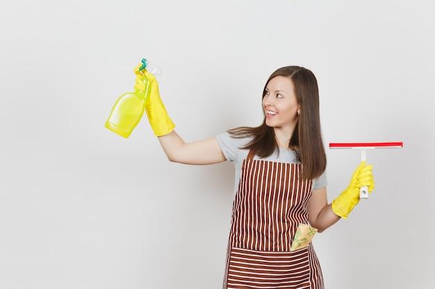 Jonge glimlachende huisvrouw in gele handschoenen, gestreepte schort, poetslap in zak geïsoleerd