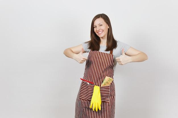 Jonge glimlachende huisvrouw in gestreepte schort met poetsdoek, rakel, gele handschoenen in zak geïsoleerd